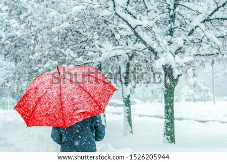 Woman under red umbrella in snow enjoying the first snowfall of the winter season