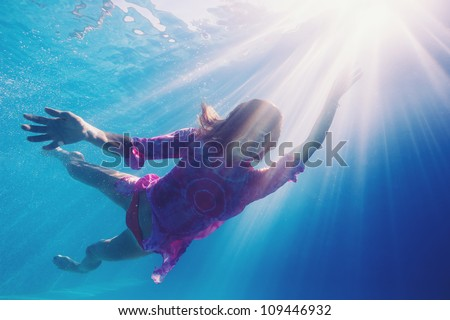 Woman underwater in swimming pool with back light.