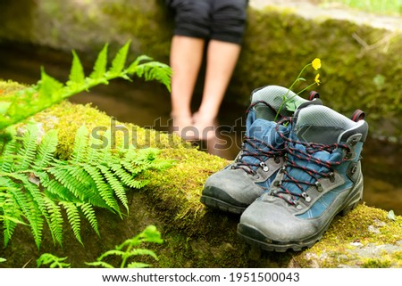 woman unfocused resting with feets on river water and hikking boots  , focus in foreground , concept relax time