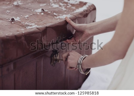 Woman Unlocking a Battered Old Trunk