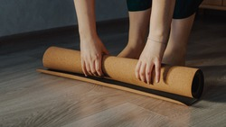 Woman unrolling cork yoga mat to practice yoga