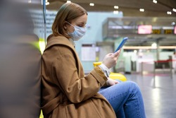 Woman upset over flight cancellation, writes message to family, sitting in almost empty airport terminal due to coronavirus pandemic/Covid-19 outbreak travel restrictions. Quarantine measure