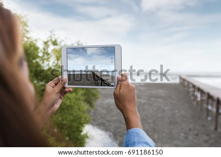 woman use digital tablet taking landscape photo