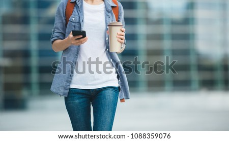 Woman use mobile phone walking with coffee themo cup in hand