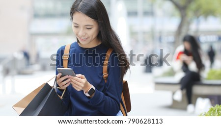 Woman use of mobile phone and holding shopping bag