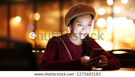 Woman use of mobile phone in coffee shop at night