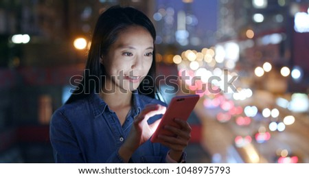 Woman use of smart phone over traffic background