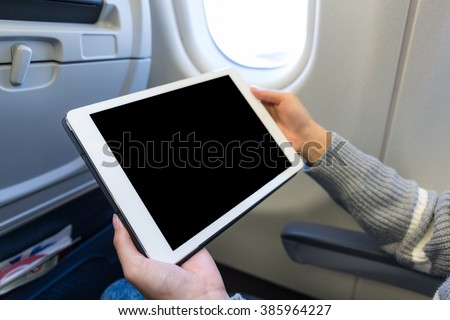 Woman use of the digital tablet in plane