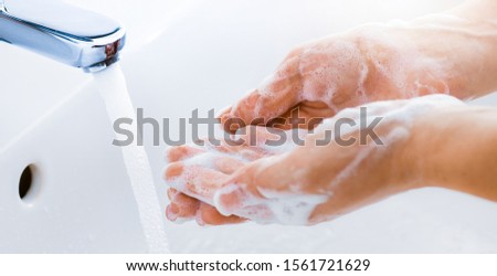 Woman use soap and washing hands under the water tap. Hygiene concept hand detail. #1561721629