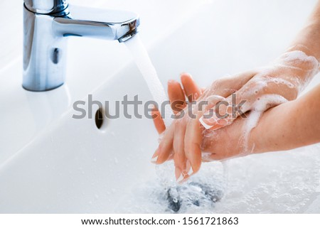 Woman use soap and washing hands under the water tap. Hygiene concept hand detail. #1561721863