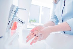 Woman use soap and washing hands under the water tap. Hygiene concept hand detail. Corona virus protection