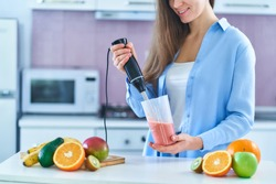Woman uses hand blender to mixing fresh fruits for prepare diet smoothie in the kitchen at home