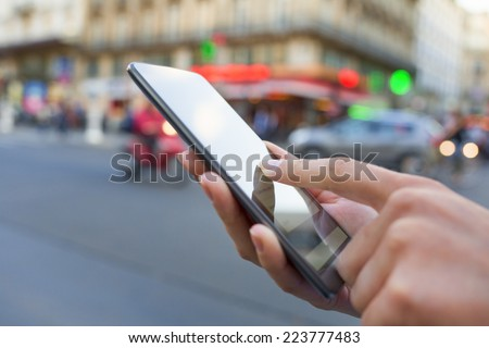 Woman uses her smart phone on the street in Paris