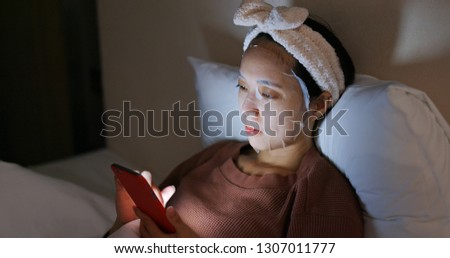 Woman uses mobile phone and applies face mask in bed at night