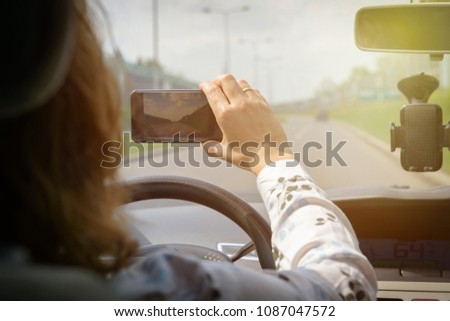 Woman uses  smart phone to record a video while driving a car. Risky driving behaviors concept