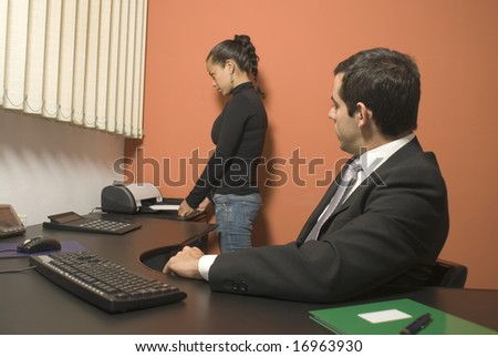 Woman using a fax machine while a businessman watches from his desk. Vertically framed photo.