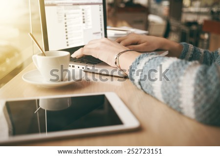 Woman using a laptop during a coffee break, hands close up
