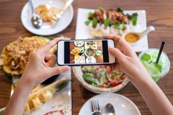 woman using a mobile camera take pictures of food placed on the table in house. After calling to order food online from home. Stay at home and shopping online during the spread of the covid-19 virus.