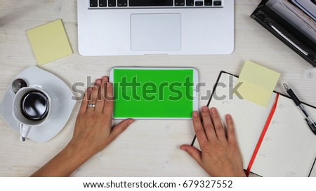 woman using a mobile phone / tablet PC with green screen at her desk in the office - top view #679327552