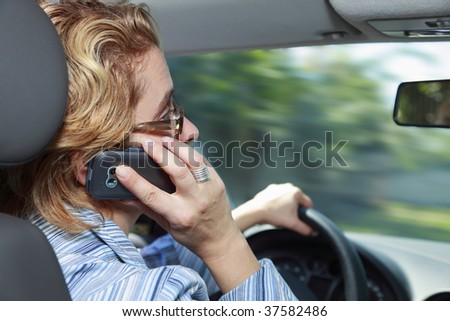 Woman using a mobile phone while she drives her car.