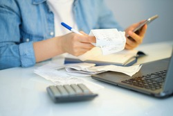 woman using a pen writing on bank account book while holding the bills to calculate in living room at home. Expenses, account, taxes, home budget concept