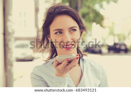 Woman using a smart phone voice recognition function online walking on a city street on a summer day  #683493121