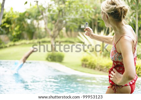 Woman using a video camera to film a man diving into a swimming pool in the garden.