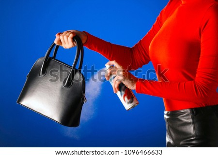 woman,using an aerosol spray for wterproofing her leather hand bag