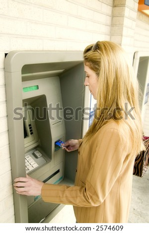 Woman using ATM to withdraw cash. - stock photo