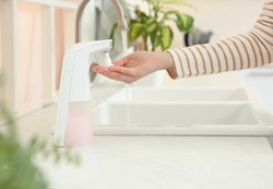 Woman using automatic soap dispenser in kitchen, closeup