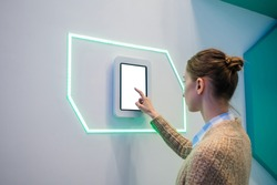 Woman using blank interactive touchscreen white display of electronic tablet kiosk at futuristic exhibition or museum. White screen, mock up, future, copyspace, template, technology concept.