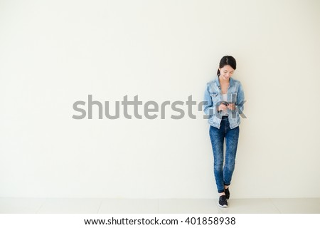 Woman using cellphone and standing against big wall