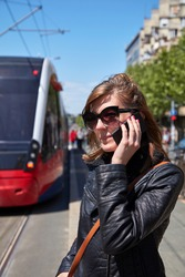 Woman using cellphone on a tram station in Europe.