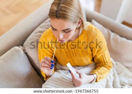 woman using cotton swab while doing coronavirus PCR test at home. Woman using coronavirus rapid diagnostic test. Young woman at home using a nasal swab for COVID-19.