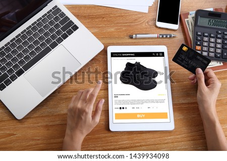 woman using credit card for buy black running shoes on e-commerce website via tablet with laptop, smartphone and office stationery on wooden desk