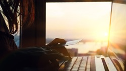 Woman using credit card online with her laptop on blurred city background during beautiful sunset and amazing sun lense flare effects