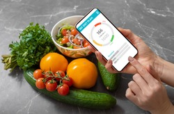 Woman using dieting app to track nutrition facts and calories in her food
