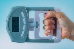 Woman Using Digital Hand Grip Dynamometer