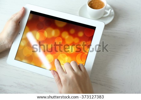 Woman using digital tablet on table close up