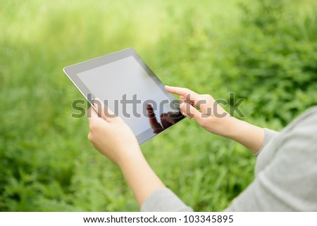 Woman using digital tablet PC in the park.