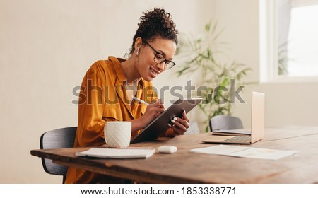 Woman using digital tablet while sitting at home. Female designer sketching on a graphic tablet while working at home.