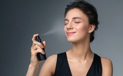 Woman using  finishing spray. Photo of woman with perfect makeup on gray background. Beauty concept