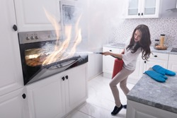 Woman Using Fire Extinguisher To Stop Fire Coming Out From Oven In Kitchen
