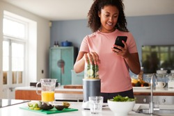 Woman Using Fitness Tracker To Count Calories For Post Workout Juice Drink He Is Making