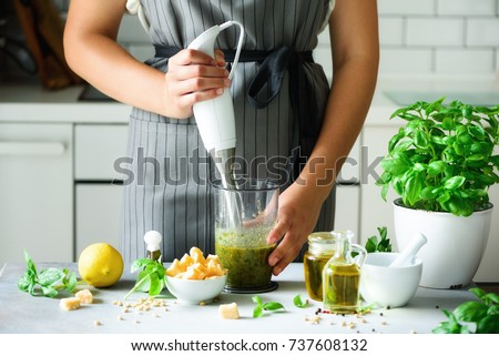 Woman using hand blender to make pesto. White kitchen interior design. Copy space. Vegetarian, clean eating lifestyle concept - Shutterstock ID 737608132