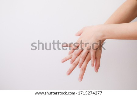 Woman using hand sanitiser on hands. The action of rubbing hand sanitiser on both hands. Importance of sanitising hands.