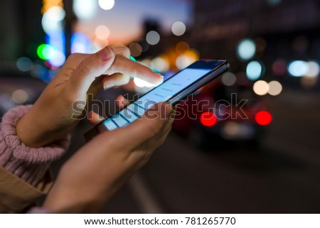 Woman using her mobile phone, city skyline night light background. Female using her mobile phone outside at night. Female hand holding touch screen mobile phone on blurred night-lights