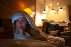 Woman using her phone under blanket in bed at night. Woman using her phone in bed at night. Light of the screen illuminating on her face. Technology, internet, communication and people concept