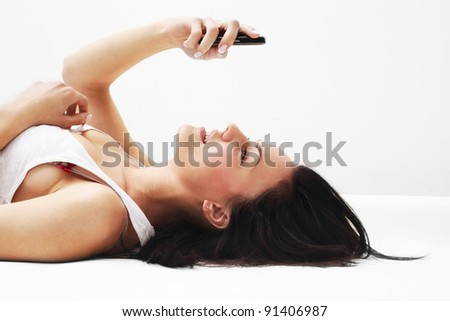 Woman using her phone while lying on her back
