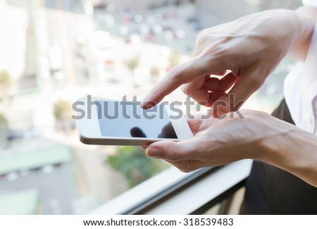 Woman using her smartphone in a elevator.